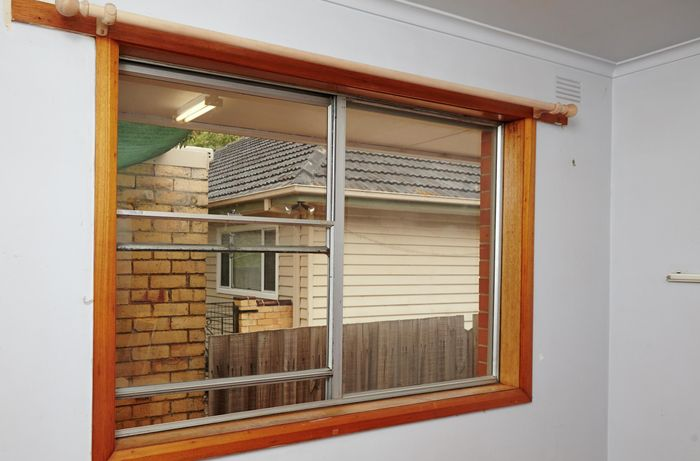 Window with brown timber frames, looking out to other houses next door.