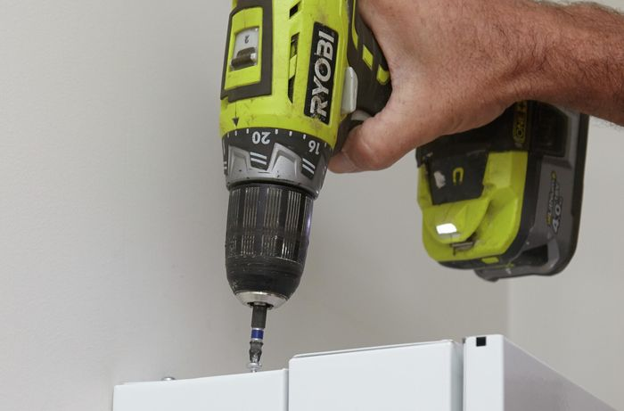 Using the drill and screws to secure the panels.