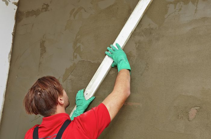 A person screeding a plastered wall with a straight edge