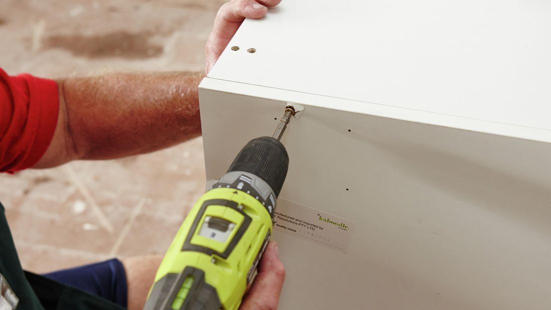 A person screwing a side panel to a cabinet using a cordless drill
