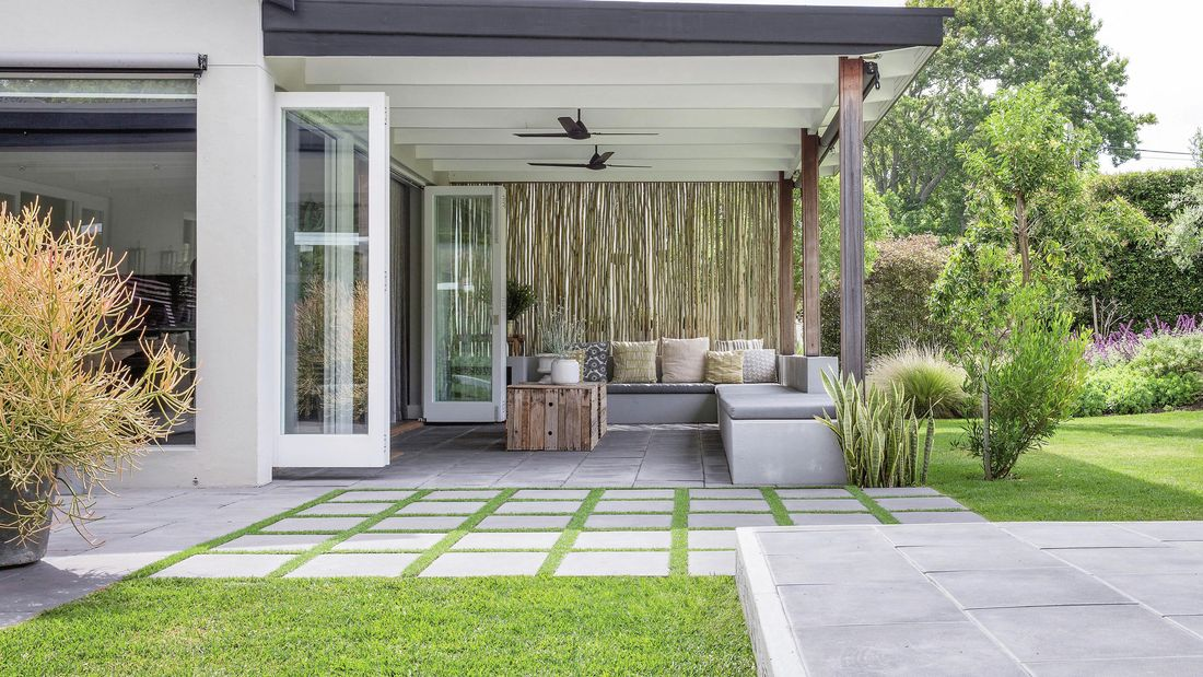 A patio space that opens from french doors, featuring geometric brick pavers on grass.