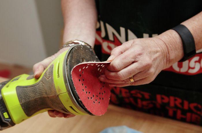 Bunnings Team Member use fine grit sandpaper on the table