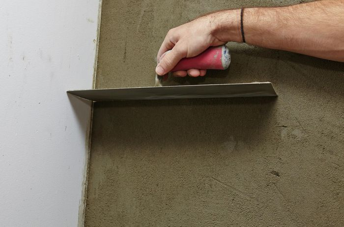 A person running a trowel down the corner of a plastered wall