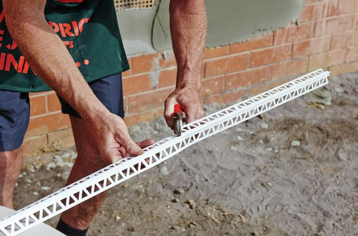 A person cutting a length of render trim bead using tin snips