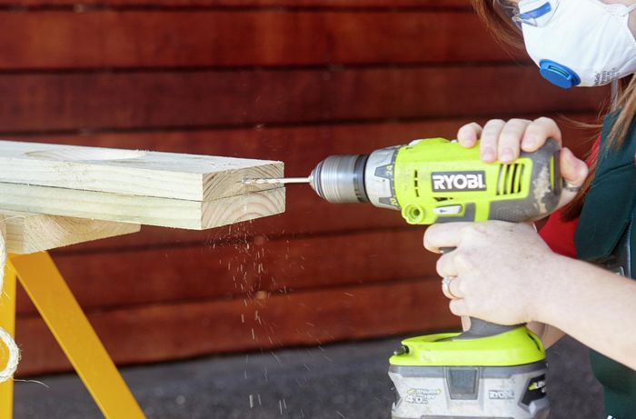 A person drilling a hole into the end of a pine board