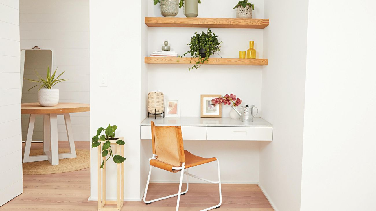 Niche space with timber floating shelves, floating desk,chair and assorted potted indoor plants
