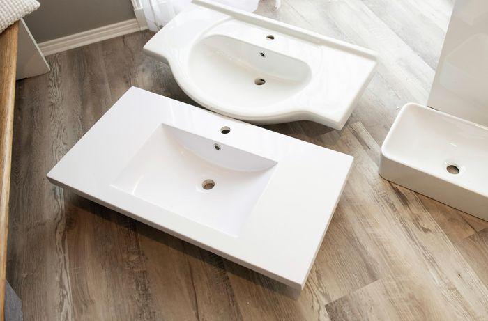Two bathroom sinks laying side by side on hardwood floor