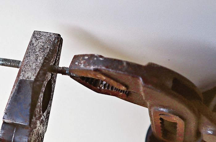Clamp and pliers holding a screw