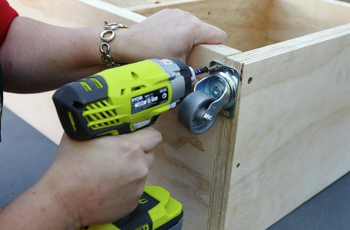 A person attaching a castor wheel to a plywood panel using a cordless drill