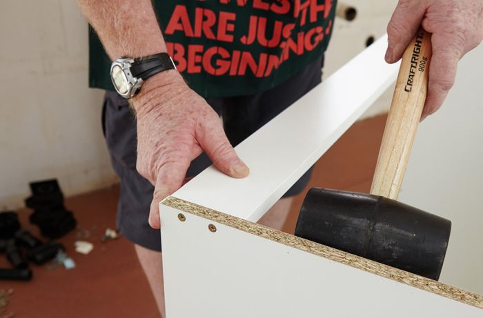 A person using a rubber mallet to position a rail in a cabinet