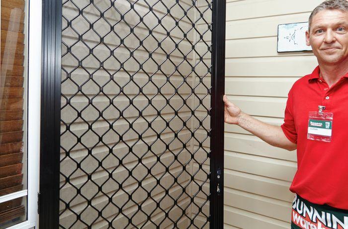 Bunnings team member Glen standing beside an aluminium screen door at the front of a house