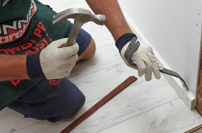Person using hammer and pinch bar to remove skirting board.