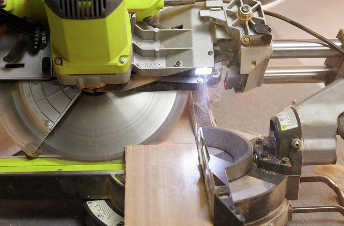 Person cutting timber on angle using circular saw