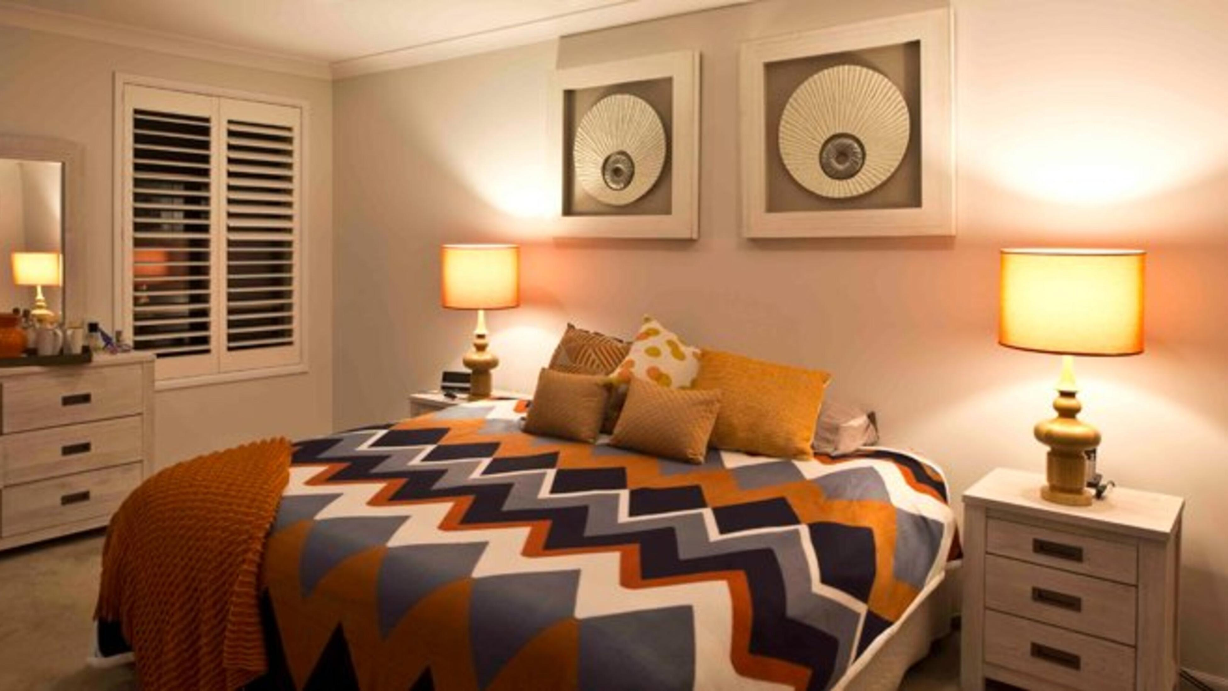 A bedroom with wall art, lamps, a dresser and shutter windows.