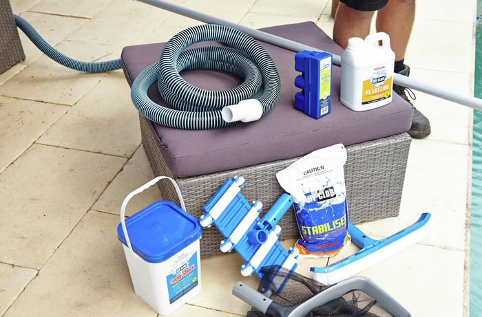 The tools and materials for maintaining a pool, including pool vacuum and hose, algaecide, pool broom, stabiliser, shock chlorine, a pool scoop, testing kit and broom handle