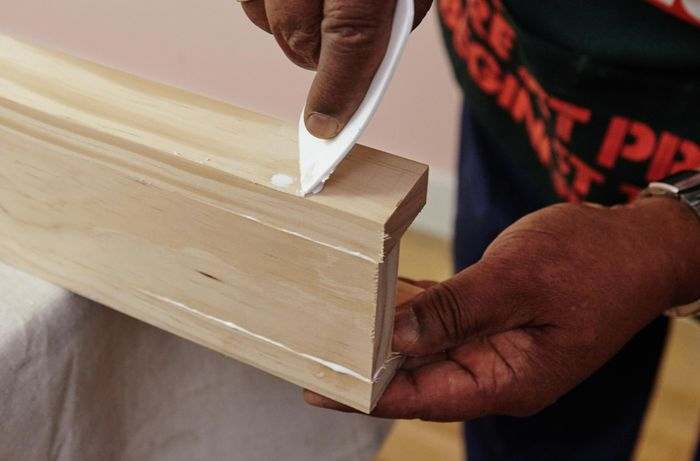 A person filling a hole in a length of pine timber with a plastic applicator