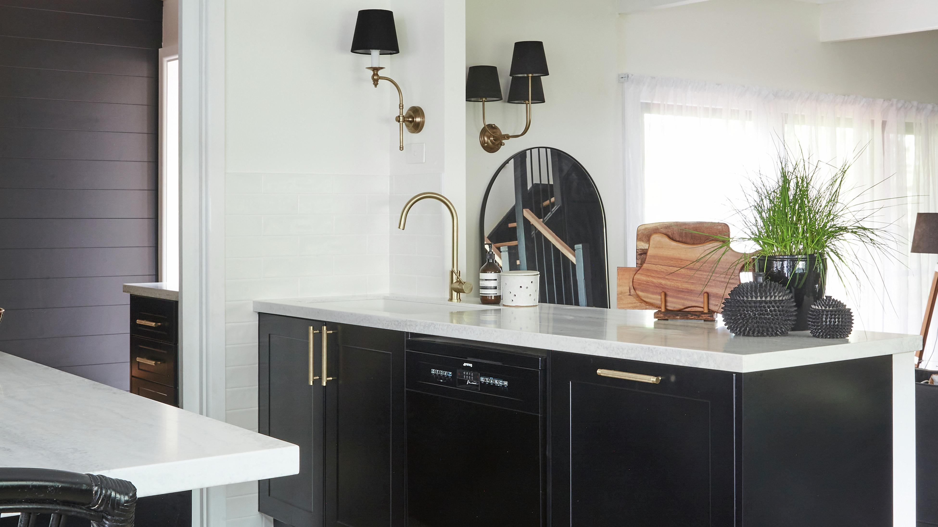 Modern monochrome ktichen with black cabinetry, gold coloured sink tap and handles
