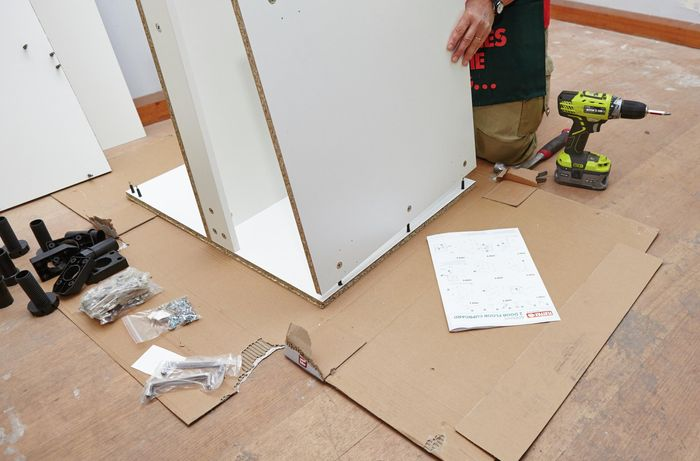 Person attaching bottom panel of cupboard