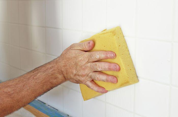Person wiping freshly tiled splashback with wet sponge.