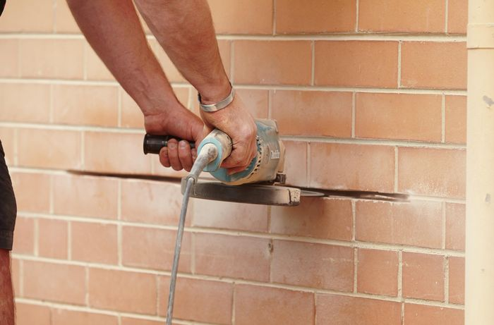 A person using an angle grinder to cut away mortar in a brick wall