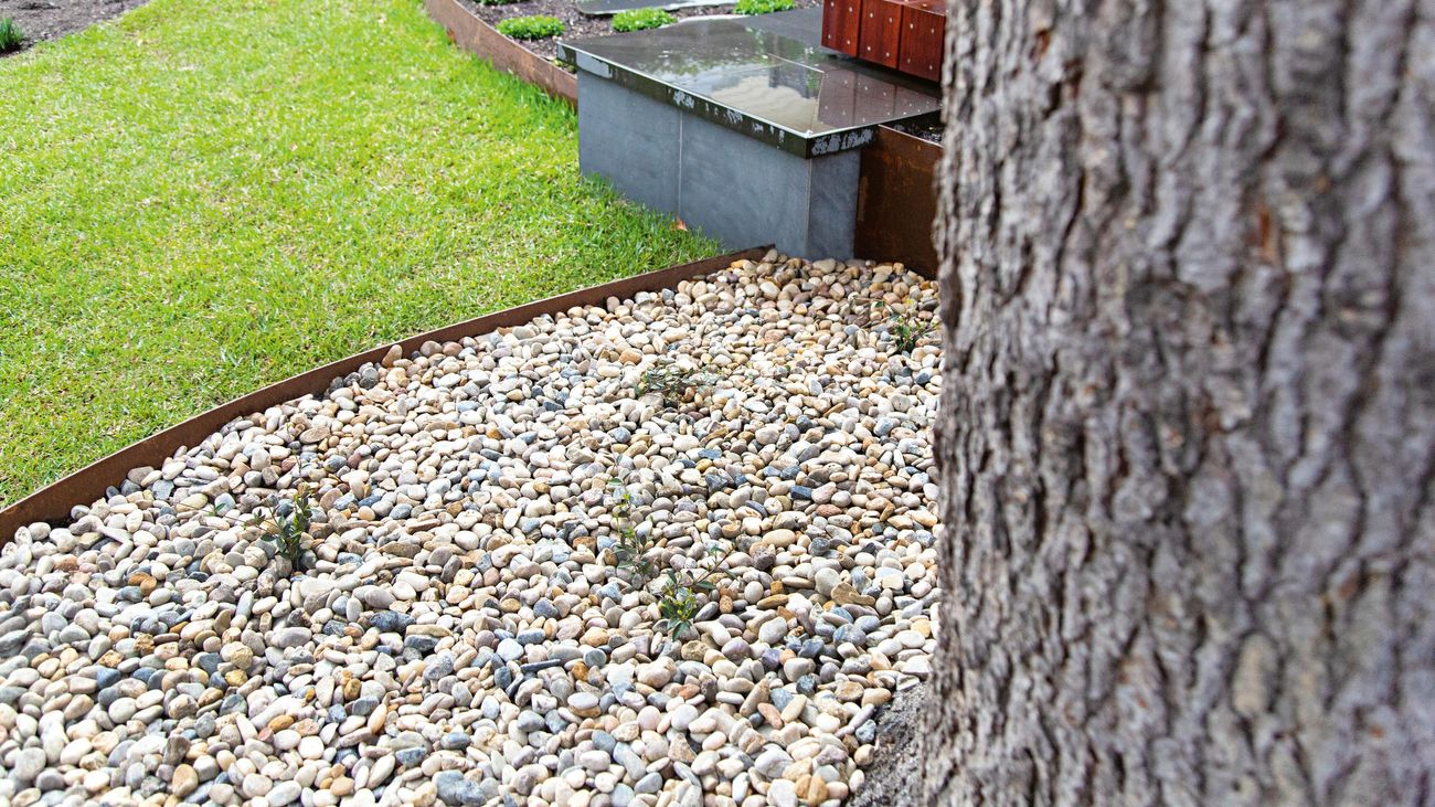 Curved garden landscaping featuring pebbles, pavers and garden edging