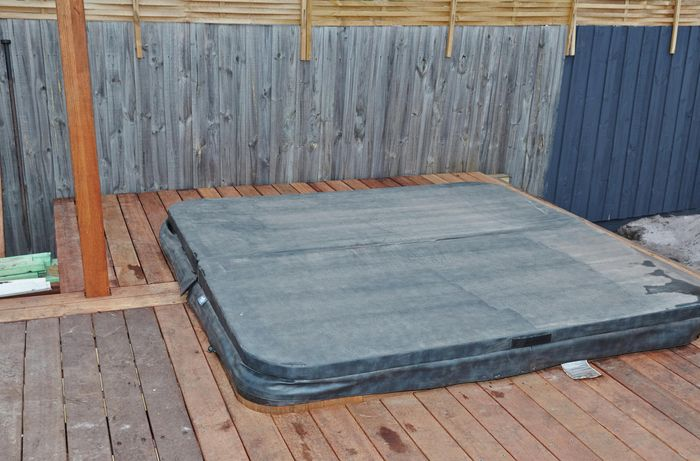 Outdoor decking area with spa that has a cover on it.