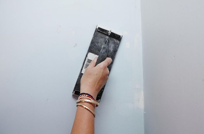 Scraping off cracked paint with a paint scraper