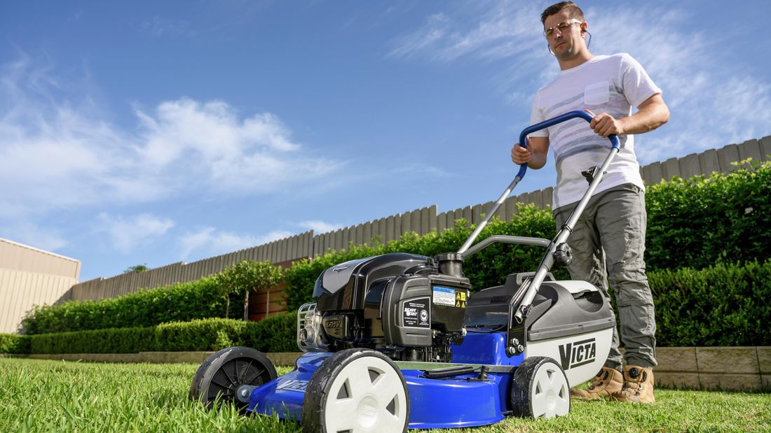 A person wearing ear and eye protection mowing grass with a Victa Power Mulcher