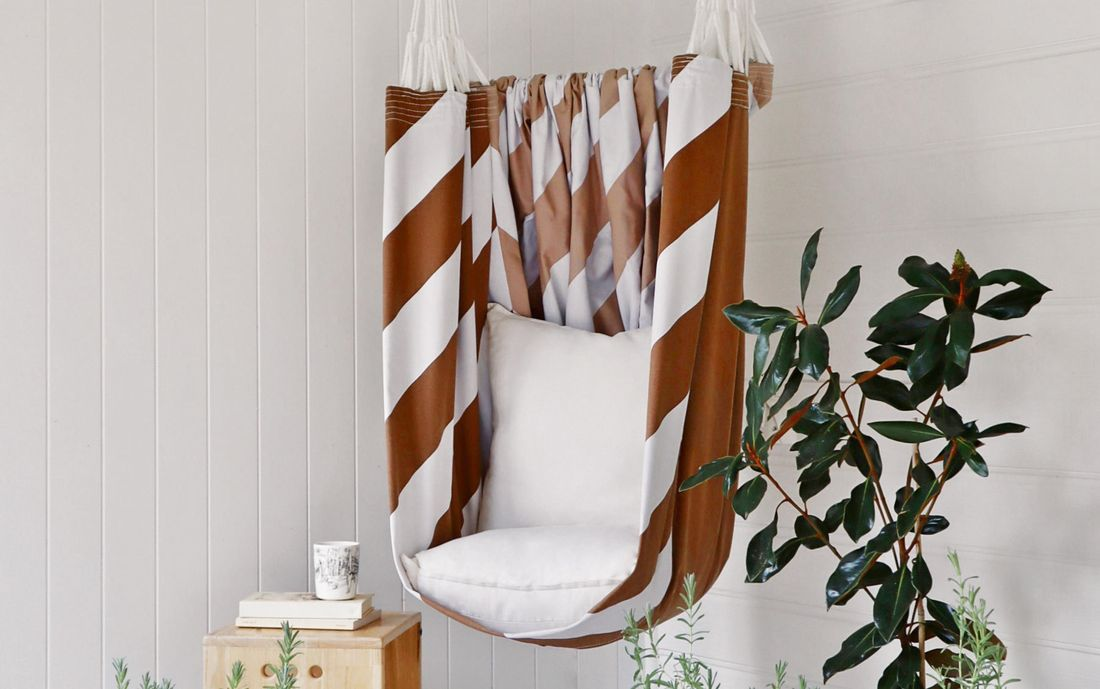 Brown and white striped hammock chair hanging in a white painted undercover area
