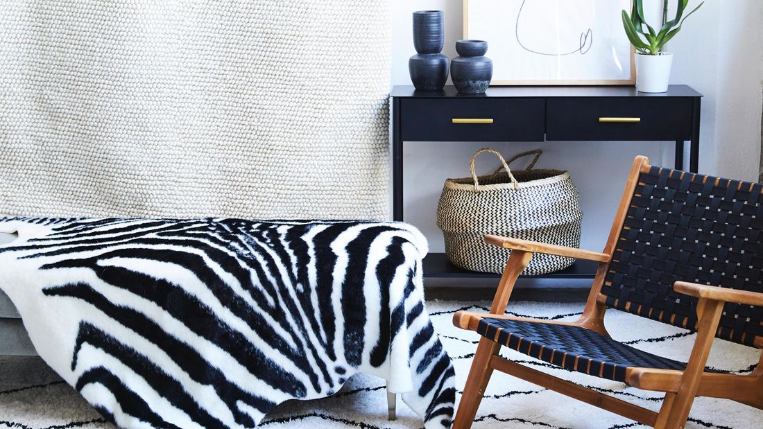 Zebra look rug draped over furniture, surrounded by black furniture and accessories with a black dog on a rug