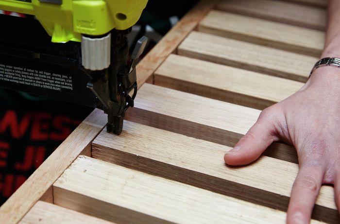 Person using nail gun to nail timber slats to frame