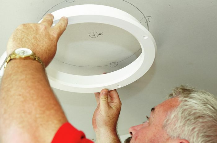 A skylight diffuser template being used to mark a hole in the ceiling to be cut to make way for Mylar tubing to come in from above