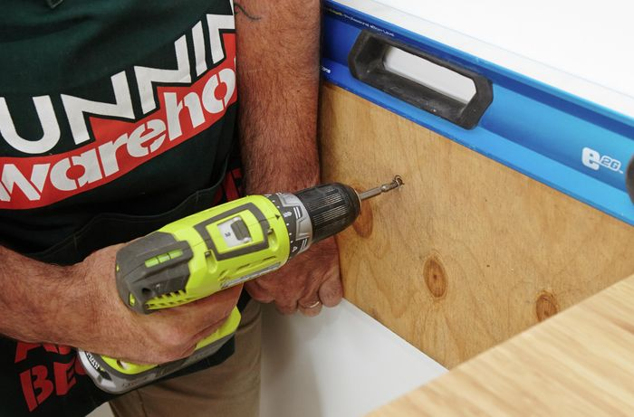 Person drilling thin piece of timber into wall.