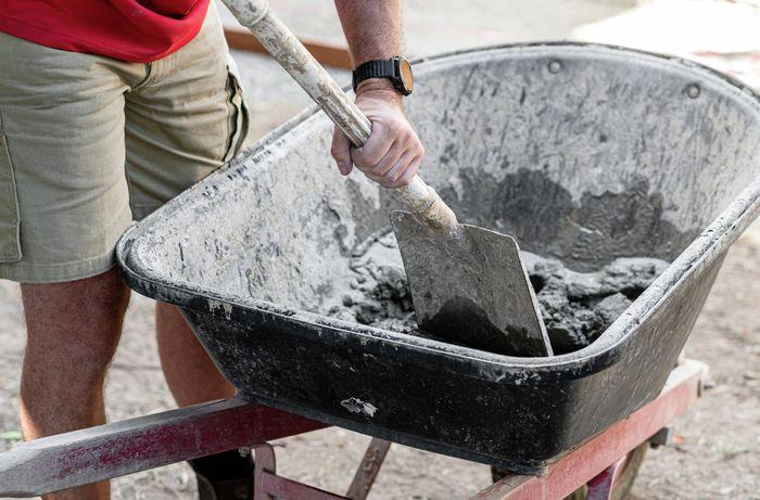 A person using a spade to mix concrete in a wheelbarrow