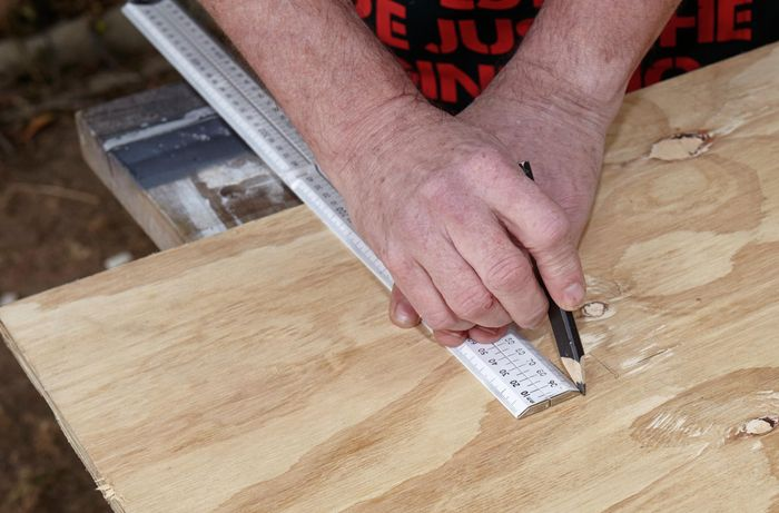 A person marking a sheet of plywood using a ruler and pencil