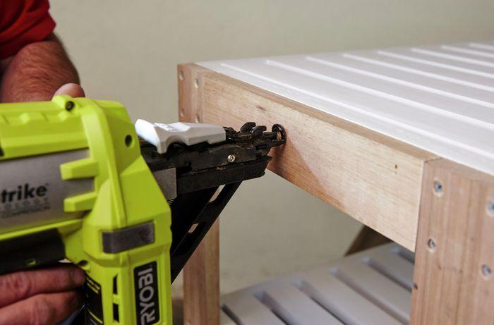Person nailing timber to shelving unit