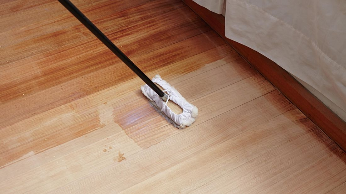 A lambswool applicator being used to apply sealer to a hardwood floor