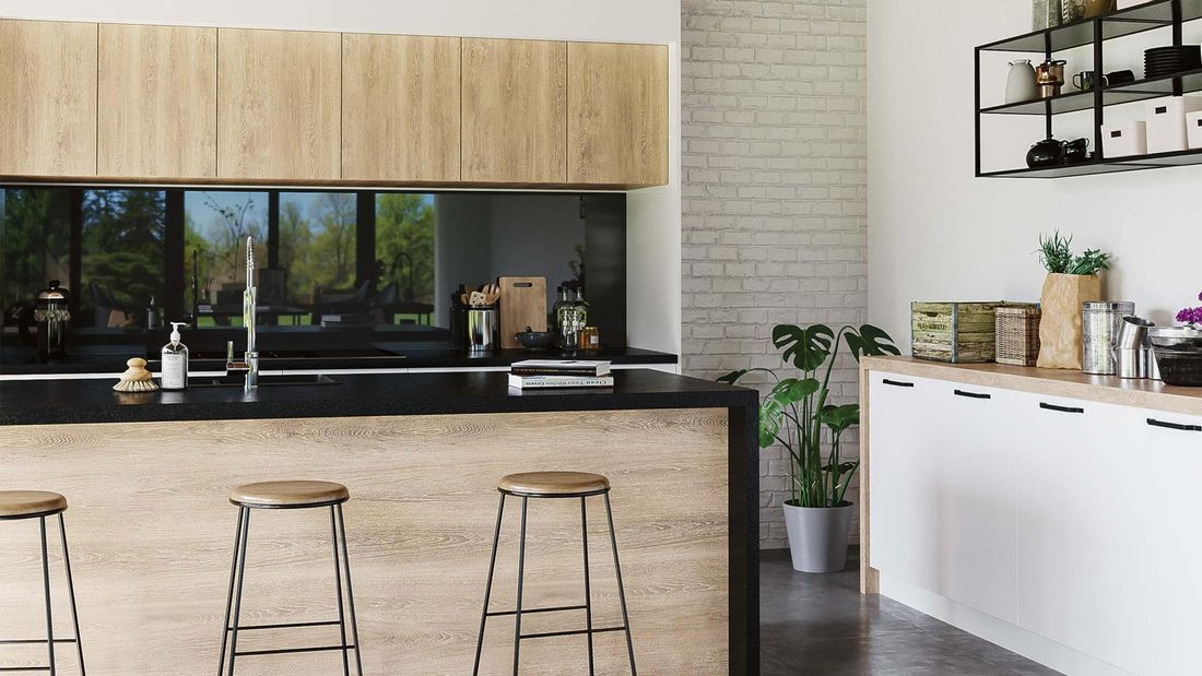 Kitchen with concrete floors, timber cabinets and black benchtop.