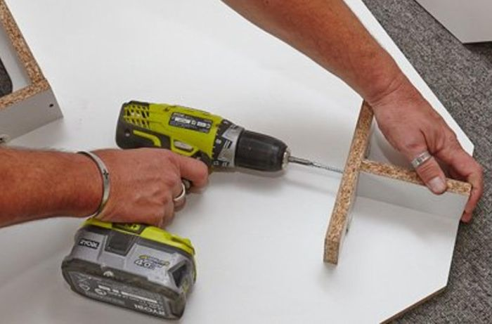 Using a drill to install the kickboards.
