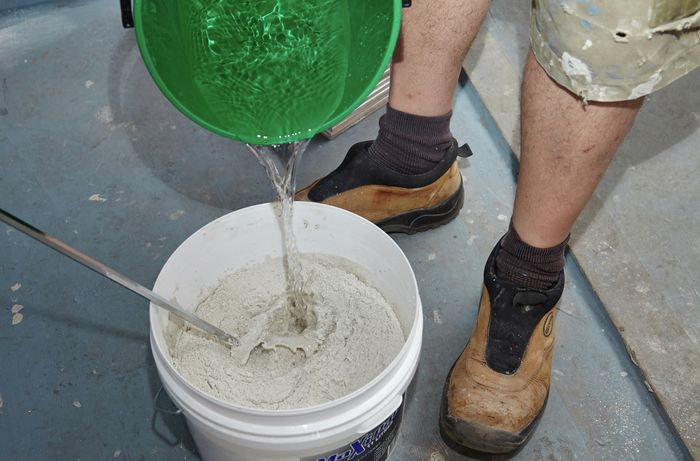 Person pouring water into bucket containing powder mastic.