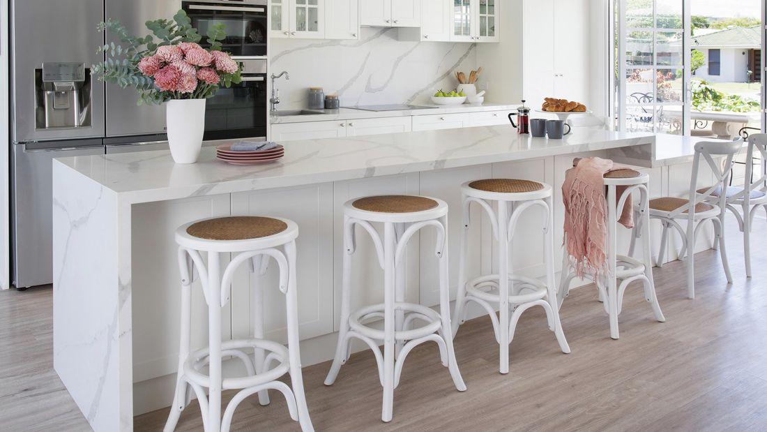 A white modern Hamptons style kitchen with white bar stools and flowers on the bench.