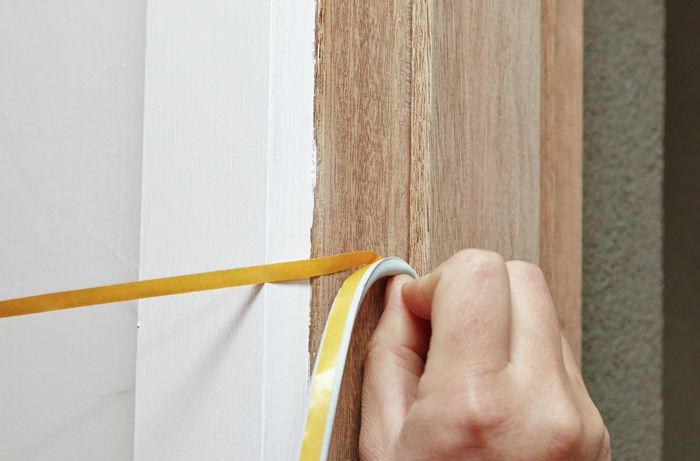 A person applying a self-adhesive draft seal around a door frame