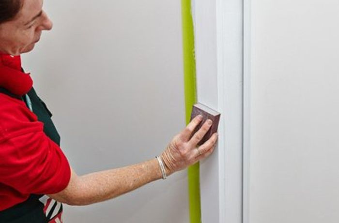 Person sanding door trims.