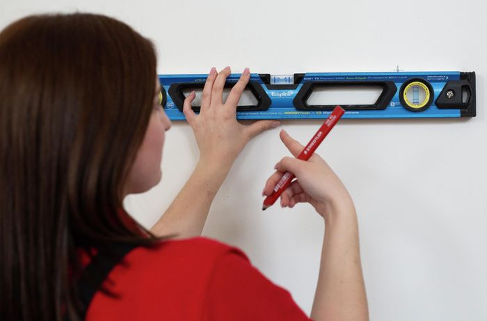 Person using a level to make marks on a wall