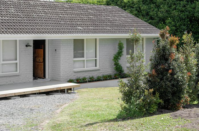 The front of a house with a gravel driveway
