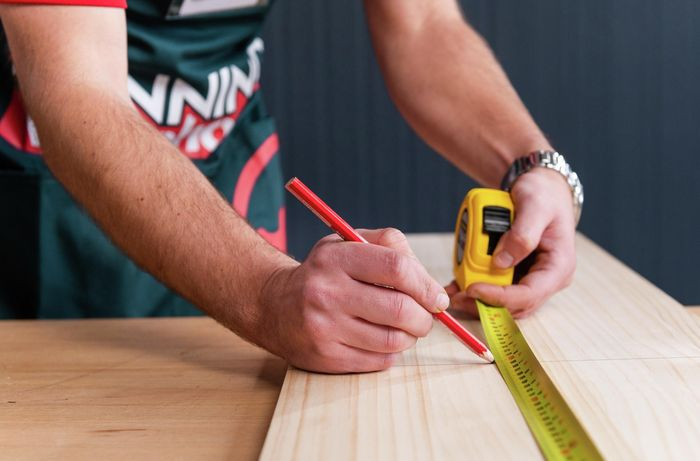 Bunnings team member measuring and marking timber with a pencil and measuring tape