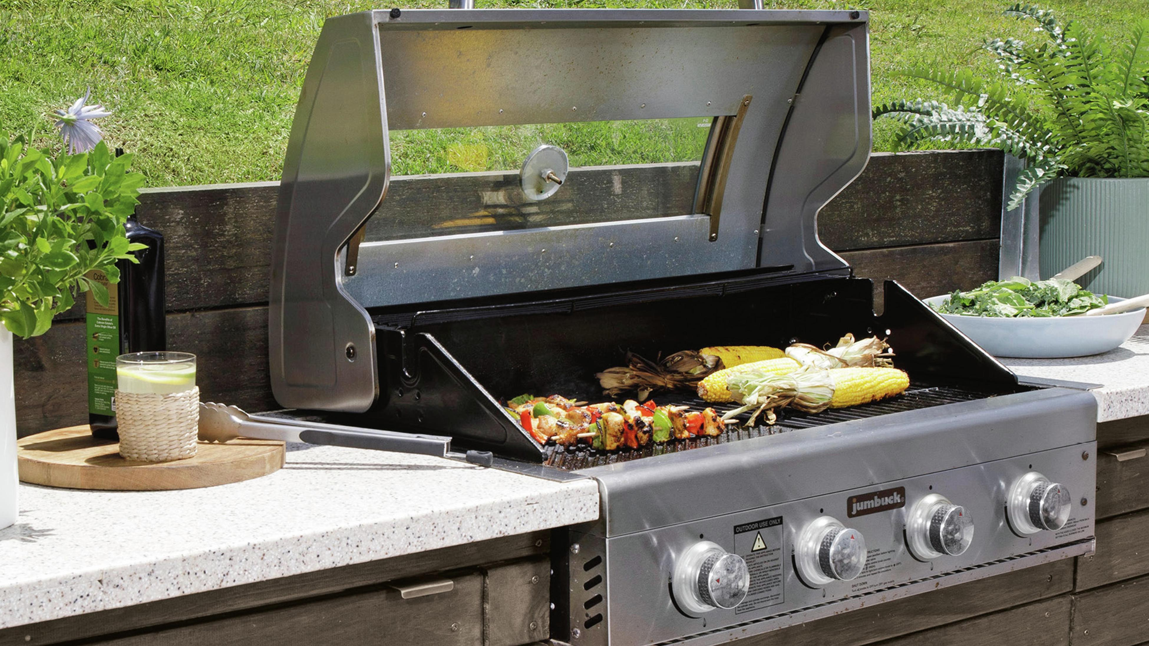 Barbecue and benchtop in outdoor space cut out of lawn slope