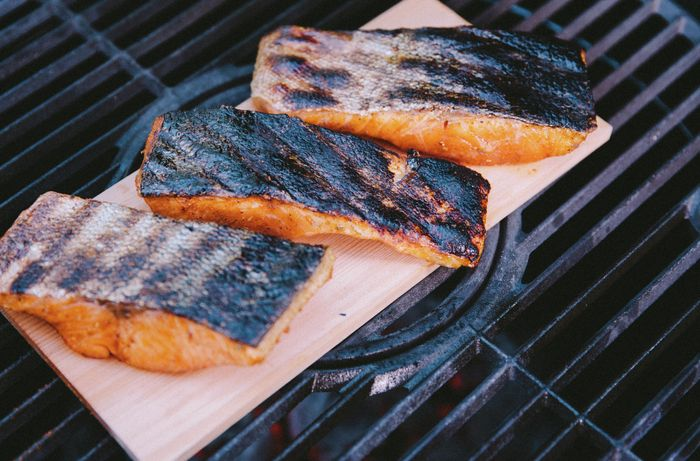 Fillets of salmon with charred skin on a grilling plank resting on a BBQ grill