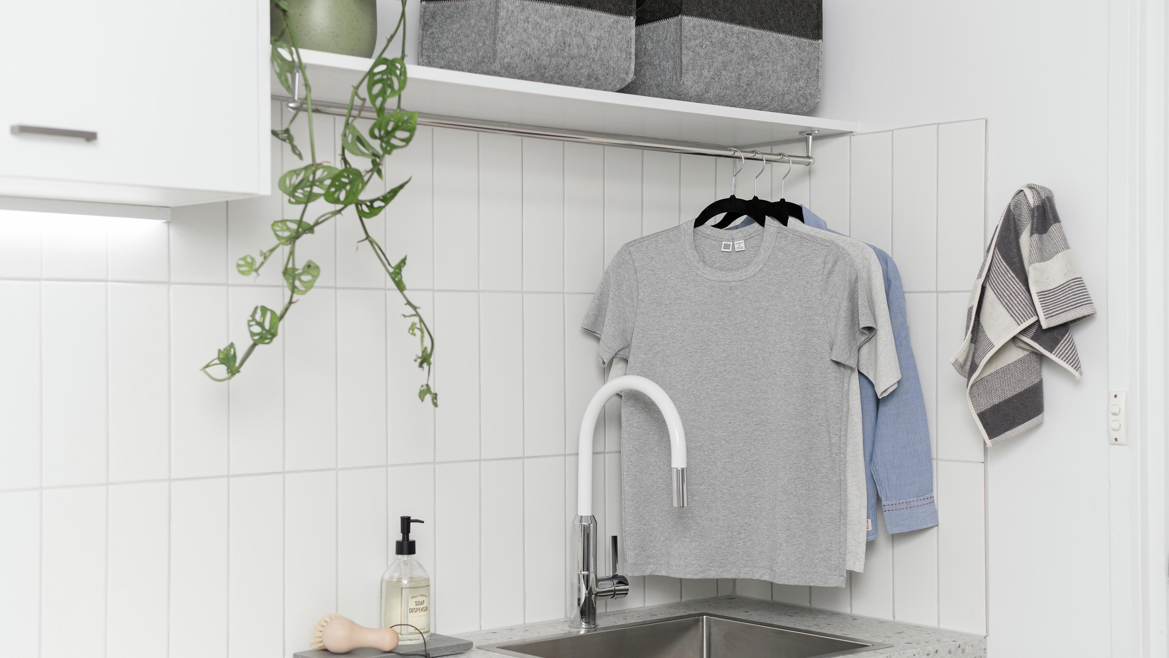 Laundry with clothing rail hanging above a sink.