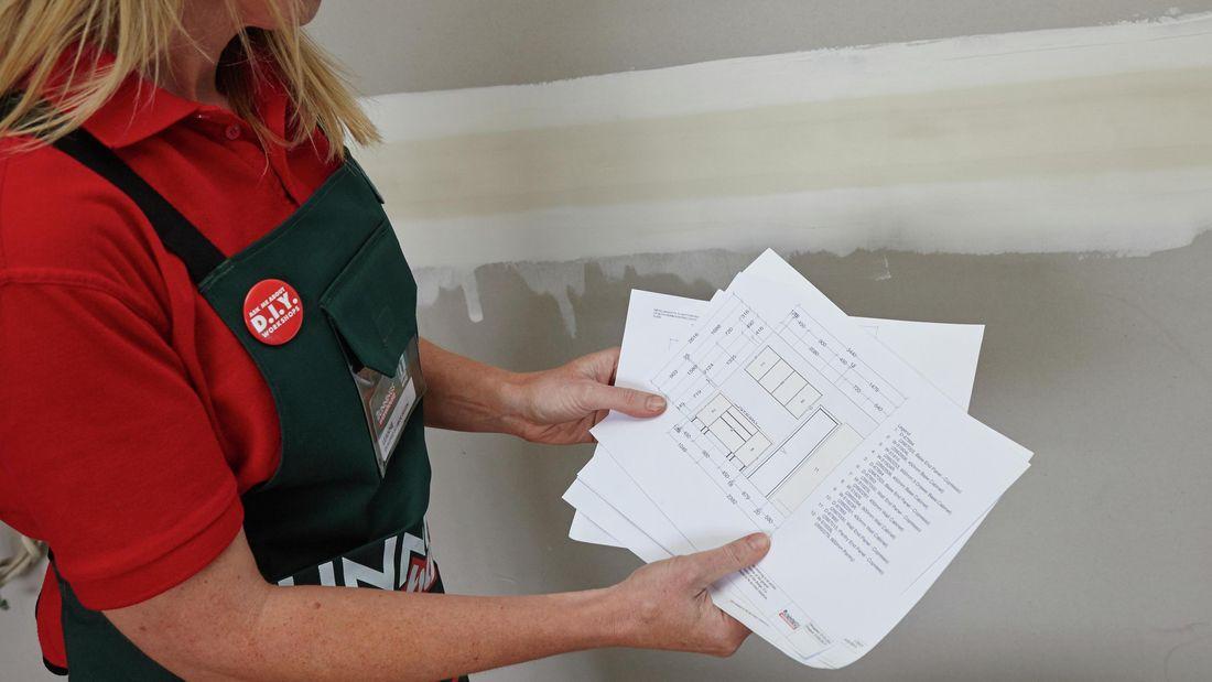 Person holding kitchen diagrams.